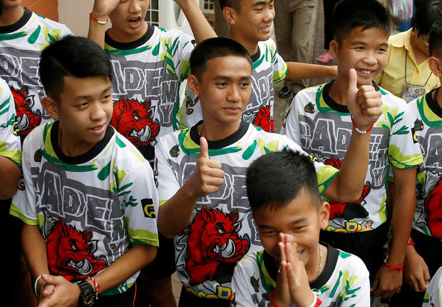 'Wild Boars' soccer players and their coach arrive for their news conference in Chiang Rai