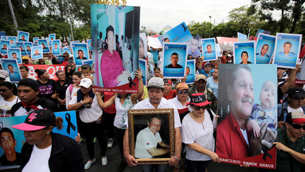 Ortega supporters hold pictures of dead police officers at demonstration in Managua