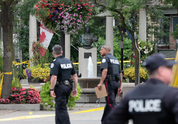 Police officers walk past Alexander the Great Parkette after a mass shooting in Toronto