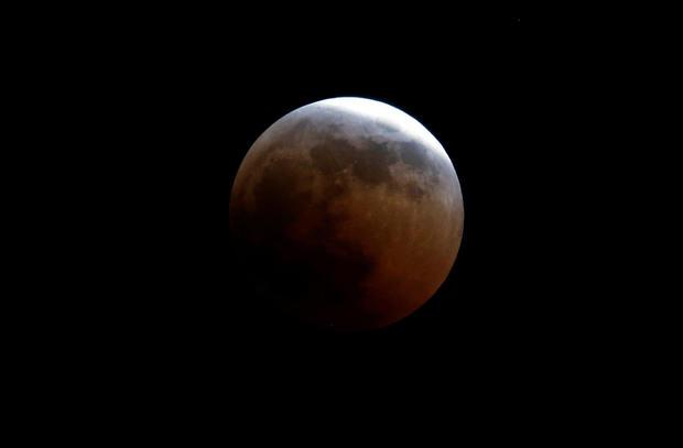 "A lunar eclipse of a full ""Blood Moon"" rises near the Oloitoktok town along the Kenya-Tanzania border"