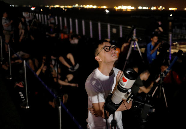 Astronomy enthusiasts wait to see the lunar eclipse of a blood moon at Marina South Pier in Singapore