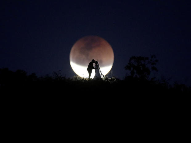 A couple poses for photo during a total lunar eclipse from in Brasilia