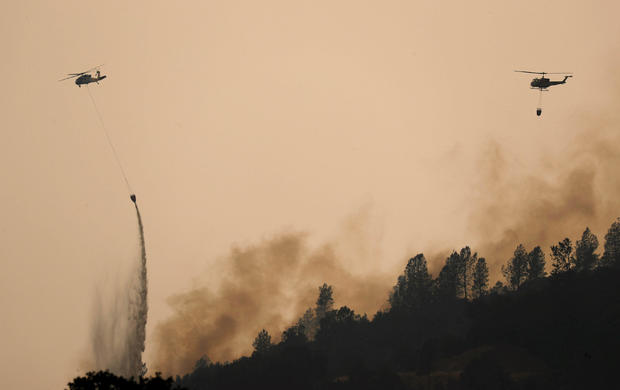 Helicopters drop water on hotspots of the Carr Fire west of Redding