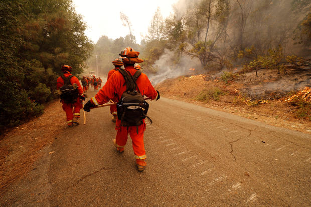 An inmate fire crew walks towards active fire while they work to stop the spread of the Carr Fire, west of Redding
