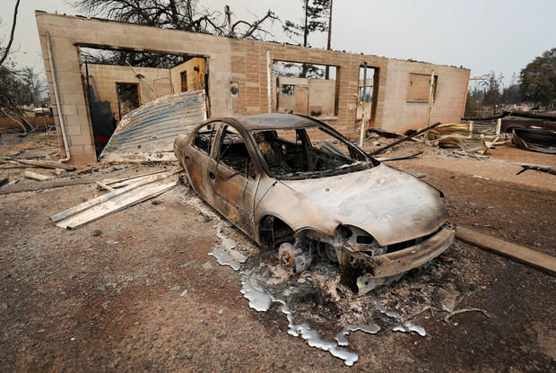 A scorched car sits next to a home that burned in the Carr Fire west of Redding