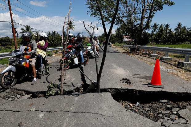 A family rides on a motorcycle through a crack on the street at Kayangan district after earthquake hit on Sunday in North Lombok