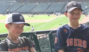 Boy gives baseball to another young boy