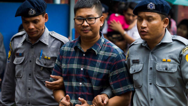 Wa Lone center gives two thumbs up as he is escorted by police to a courtroom for his on going trial in Yangon