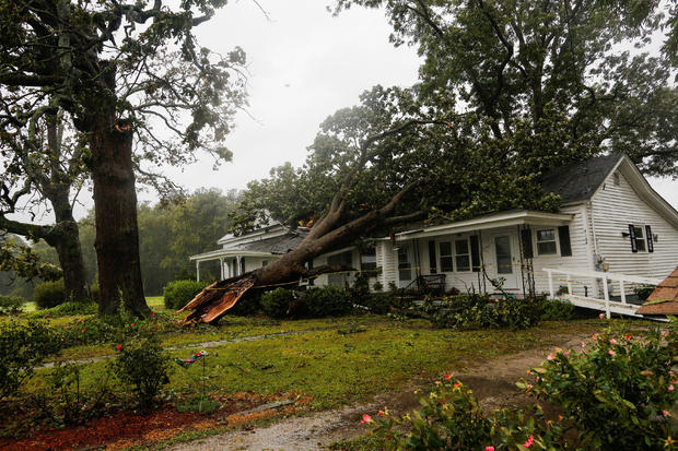 A downed tree rests on a house during the passing of Hurricane Florence in the town of Wilson