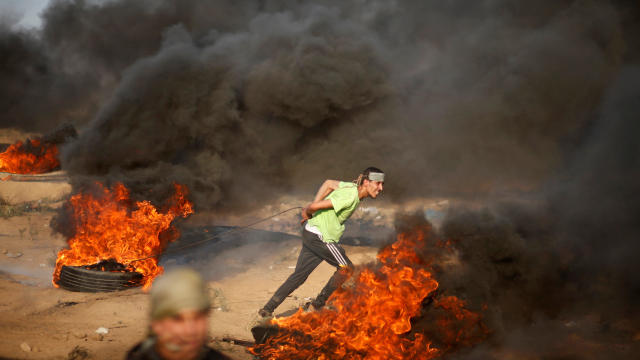 Palestinian demonstrator pulls a burning tyre during a protest at the Israel-Gaza border fence east of Gaza City