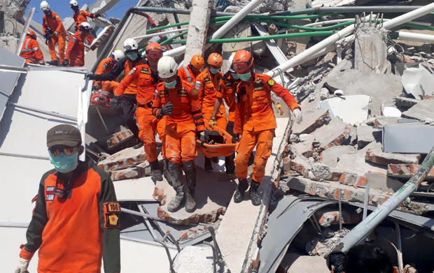 A search and rescue team evacuates a victim from the ruins of the Roa-Roa Hotel in Palu, Central Sulawesi,