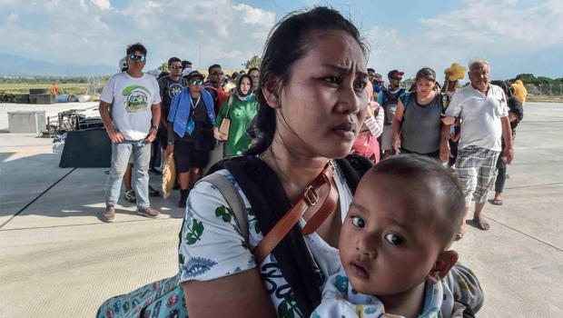 People injured or affected by the earthquake and tsunami wait to be evacuated on an air force plane in Palu, Central Sulawesi