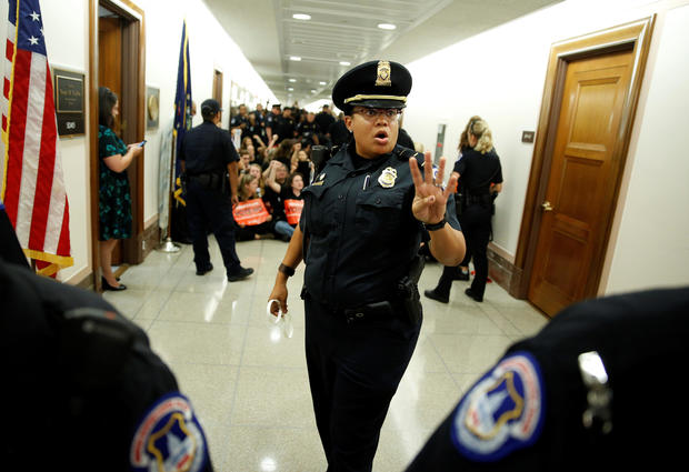 A police officer clears the hallway before demonstrators are arrested as they protest against U.S. Supreme Court nominee Brett Kavanaugh in front of the office of Senator Susan Collins (R-ME) on Capitol Hill in Washington