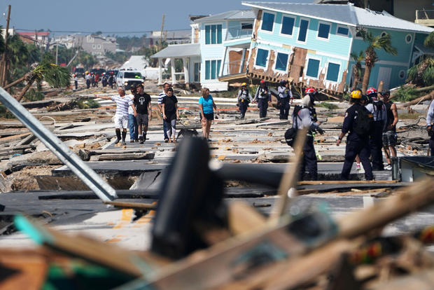 First responders and residents walk along a main street following Hurricane Michael in Mexico Beach