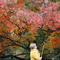 A woman takes a selfie at Moscow State University's Botanic Garden (Apothecary Garden) in autumn foliage in Moscow