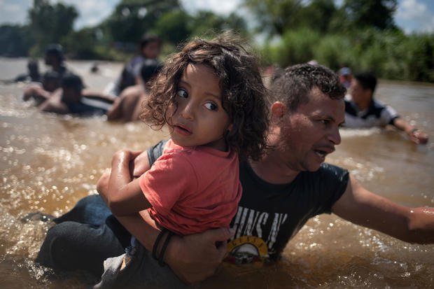 Migrant carries girl through the Suchiate River into  Mexico from Guatemala in Ciudad Hidalgo, Mexico