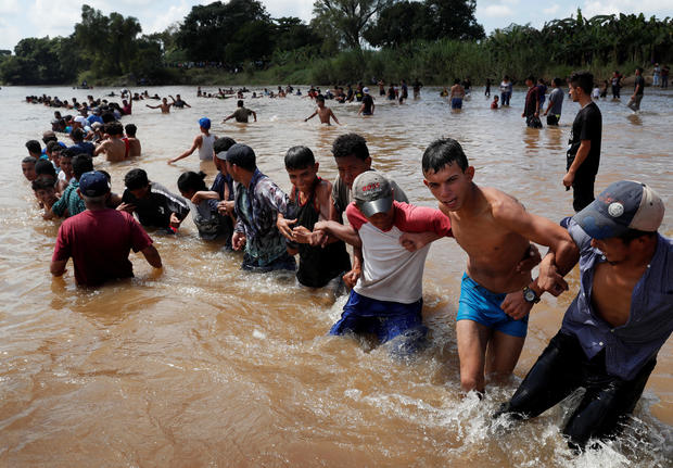 Migrants, part of a caravan travelling to the U.S., make a human chain to pull people from the river between Guatemala to Mexico in Ciudad Hidalgo and continuing to walk in Mexico