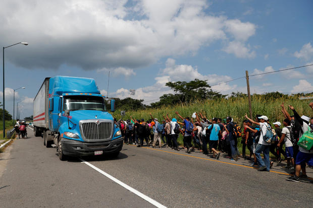 Migrants, part of a caravan traveling from Central America en route to the United States, wave to a truck while walking by the road that links Ciudad Hidalgo with Tapachula