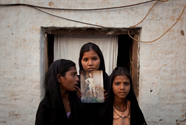 FILE PHOTO: The daughters of Pakistani Christian woman Asia Bibi pose with an image of their mother while standing outside their residence in Sheikhupura Pakistan