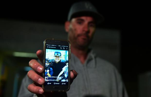 Jason Coffman displays a photo of his son Cody outside the Thousands Oaks Teen Center where he came hoping to find his son who was at the Borderline Bar and Grill in Thousand Oaks, California, on Nov. 8, 2018.