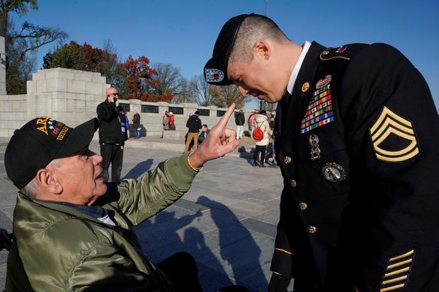 Vietnam war Army veteran Larry Dawson talks about the beret worn by Army Sergeant First Class Ryan Mata at World War II Memorial on Veterans Day in Washington