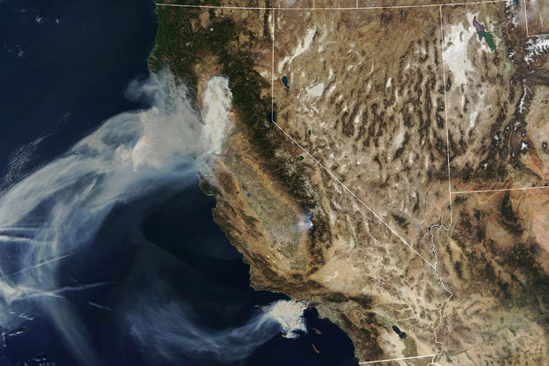 A NASA Terra satellite image shows smoke continuing to spread west from the Camp Fire and two more fires, the Hill and Woolsey Fires in southern California