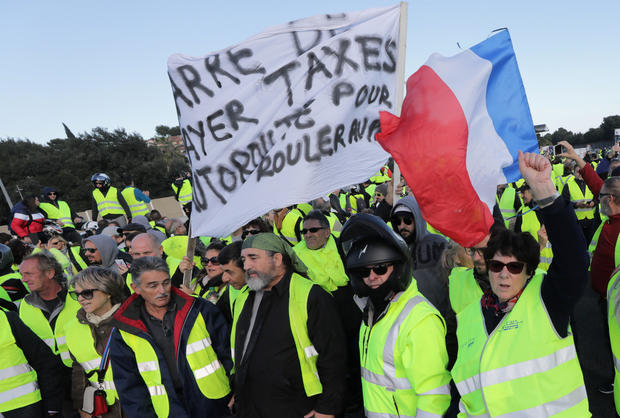 People wearing yellow vests, a symbol of a French drivers' protest against higher fuel prices, block the motorway in Antibes