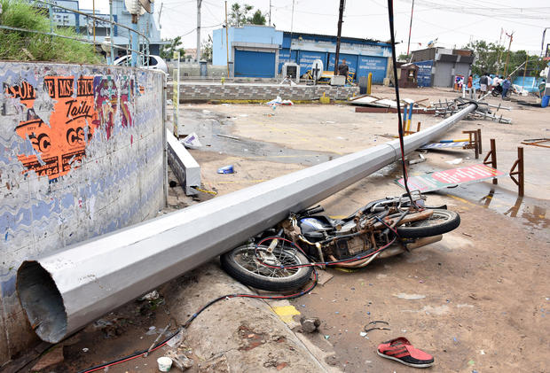 A fallen pole and a damaged motorbike are seen in a road after cyclone Gaja hit Velankanni