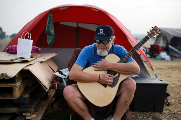 Kelly Boyer plays a guitar he was given outside his tent near a Walmart in Chico, California, after the Camp Fire destroyed his home in Paradise, Nov. 20, 2018.