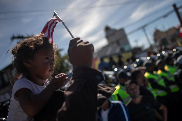 A migrant girl, part of a caravan of thousands from Central America, sits on top of her father as they are surrounded by police while marching to the United States border with Mexico in Tijuana