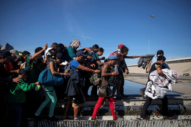 Migrants, part of a caravan of thousands traveling from Central America en route to the United States,cross the Tijuana river to reach the border wall between the U.S. and Mexico in Tijuana