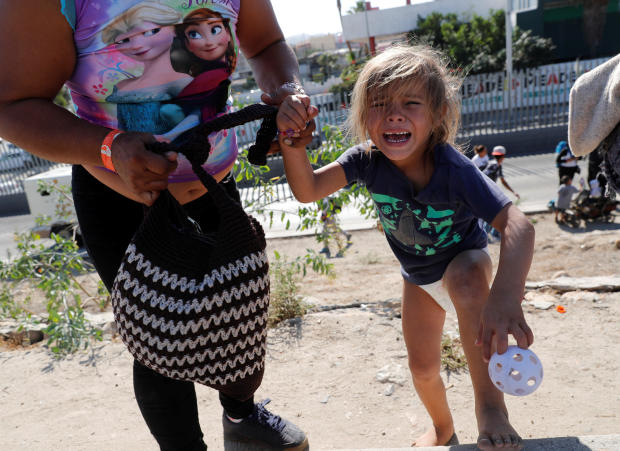 A migrant girl from Honduras, part of a caravan of thousands traveling from Central America en route to the United States, cries after running away from tear gas thrown by the U.S. border control near the border wall between the U.S. and Mexico in Tijuana