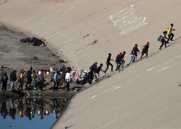 Migrants, part of a caravan of thousands from Central America trying to reach the United States, make their way to the border fence between Mexico and the United States in Tijuana