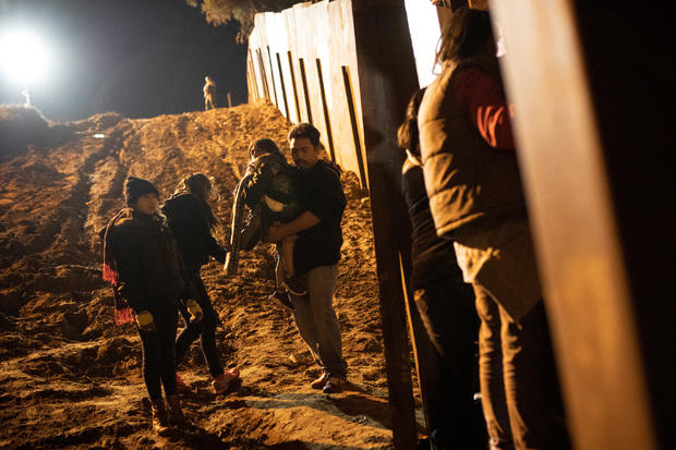 Migrants, part of a caravan of thousands from Central America trying to reach the United States, are seen in San Diego County, U.S., after crossing illegally from Mexico to the U.S by jumping a border fence, photographed through the border wall in Tijuana