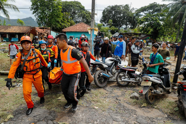 Rescue workers carry a body bag containing remains of a victim of a tsunami at the beach front hotel in Pandeglang