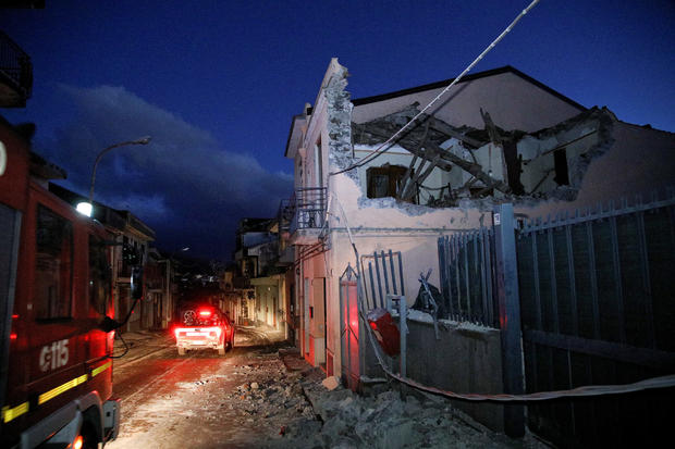Fire fighters are seen next to a house damaged by an earthquake, measuring magnitude 4.8, at the area north of Catania on the slopes of Mount Etna in Sicily