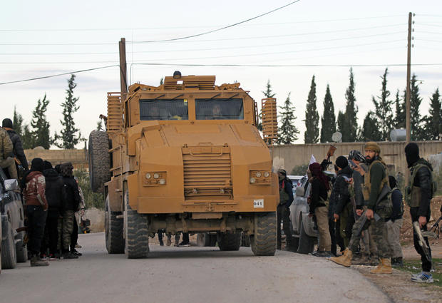 Turkish soldiers ride a military vehicle at Manbij countryside