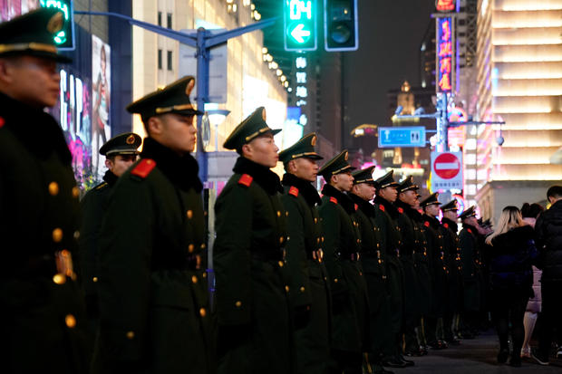 Paramilitary police stand guard near the Bund on New Year's Eve, in Shanghai