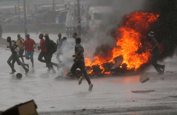 FILE PHOTO: People run at protest as barricades burn during rainfall in Harare