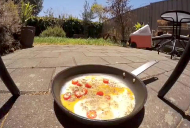 A pan with frying eggs is seen on a pavement during a heatwave in Adelaide