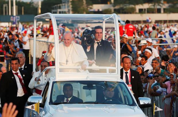 Pope Francis waves from his Popemobile as he arrives for a vigil at Saint Paul II Metro Park during World Youth Day in Panama City