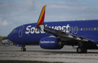 Travelers wait in line to check in at the Southwest Airlines