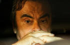 Former Nissan Motor Chairman Carlos Ghosn sits inside a car as he leaves his lawyer's office after being released on bail from Tokyo Detention House, in Tokyo
