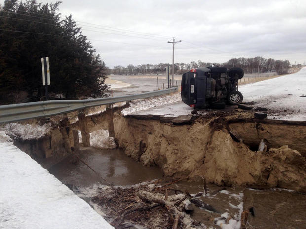 ​An overturned vehicle is seen on a washed-out road in a picture posted to a Nebraska State Patrol Twitter account on March 14, 2019.