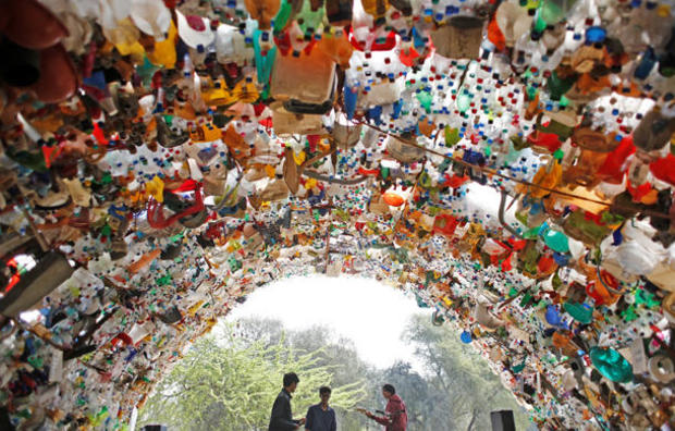 Students perform under a shade made from used plastic bottles as they take part in a global protest against climate change in Gurugram