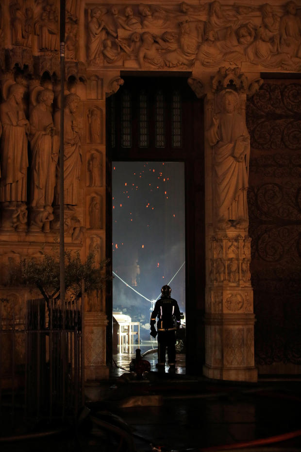 A Paris Fire brigade member is seen in a doorway as he looks into the Notre Dame Cathedral as a fire continues to burn in Paris