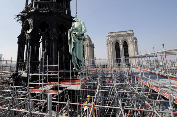 FILE PHOTO: A statue of Saint John is removed from the spire of Notre Dame cathedral by a crane before restoration work, in Paris