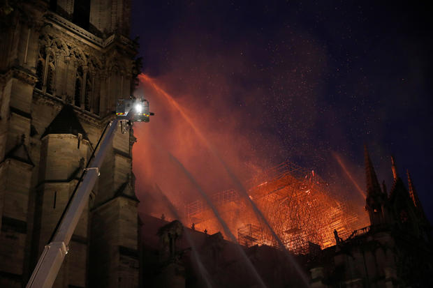Paris Fire brigade members spray water to extinguish flames as the Notre Dame Cathedral burns in Paris