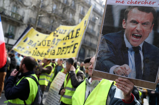 A protester holds an image of French President Emmanuel Macron shouting during an anti-government demonstration called by the so-called yellow vest (gilets jaunes) movement in Paris, on March 23, 2019.