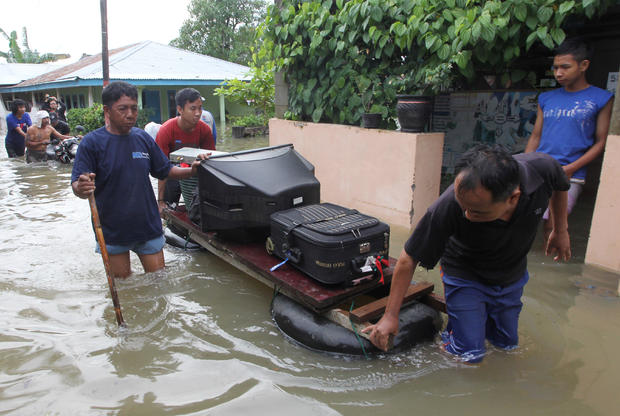 Residents carry their belongings with a raft through the flood in Bengkulu